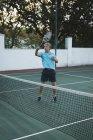 Vista lateral de hombre senior de tenis en cancha de tenis - foto de stock
