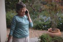 Старшая женщина разговаривает по мобильному телефону на заднем дворе — стоковое фото