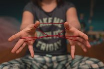 Mid section of girls hand making cats cradle at home — Stock Photo