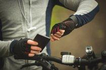 Partie médiane du temps de contrôle du cycliste lors de l'utilisation du téléphone portable en forêt — Photo de stock
