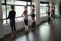 Gruppo di donne che allungano che tiene la sbarra in palestra — Foto stock