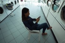 Young woman using her phone while waiting at laundromat — Stock Photo