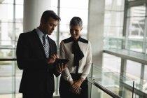 Deux hommes d'affaires discutant sur la tablette au bureau — Photo de stock