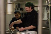 Chefs masculinos preparando comida na cozinha no restaurante — Fotografia de Stock