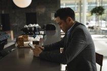 Empresário usando seu telefone no balcão da cafetaria no escritório — Fotografia de Stock