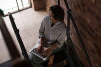 Attentive woman using laptop on staircase at home — Stock Photo