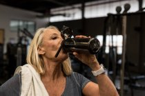 Disabled mature woman drinking water in the gym — Stock Photo