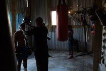 Trainer, die Unterstützung der männlichen Boxer tragen Kopfbedeckungen im Fitness-studio — Stockfoto