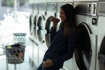 Smiling woman talking on the phone at laundromat — Stock Photo