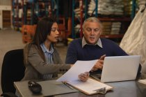 Staff interacting with each other over documents in warehouse — Stock Photo