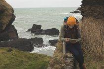 Konzentrierte Wanderin liest Landkarte und trinkt — Stockfoto