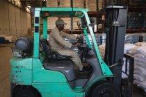 Seção intermediária do trabalhador masculino dirigir empilhadeira em armazém — Fotografia de Stock