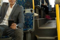 Mid section of man using mobile while travelling in the bus — Stock Photo