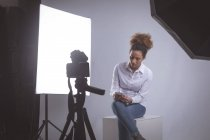 Female photographer using mobile phone in photo studio — Stock Photo