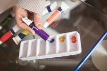 Gros plan de la femme utilisant la couleur du tube à la maison — Photo de stock