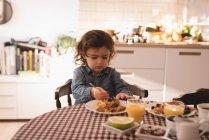 Маленькая девочка, имея завтрак на кухне дома — стоковое фото