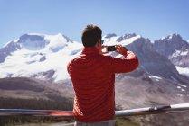 Homem tirando foto com celular em um dia ensolarado — Fotografia de Stock