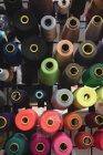 Hilos multicolores de primer plano dispuestos en fila en la sastrería - foto de stock