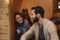 Glückliches Paar interagiert beim Kaffeetrinken am Eingang des Blockhauses — Stockfoto