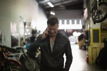 Mechanic talking on mobile phone in garage — Stock Photo