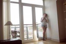 Femme réfléchie buvant du café le matin dans le salon à la maison . — Photo de stock