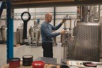 Männliche Arbeiter Check-Maschine der Brennerei in Fabrik — Stockfoto