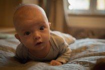 Портрет милого ребенка, лежащего на кровати в спальне — стоковое фото