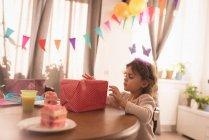 Маленька дівчинка, дивлячись на коробці подарунка у вітальні на дому — стокове фото