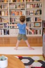 Rear view of little girl performing stretching exercise in living room at home — Stock Photo