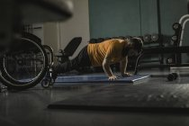 Handicapped man doing pushup on mat in gym — Stock Photo
