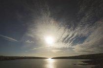 Belo pôr do sol e nuvens sobre o lago na zona rural — Fotografia de Stock