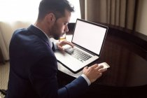 Businessman using mobile phone while working on laptop in hotel — Stock Photo