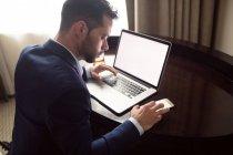 Empresario que utiliza el teléfono móvil mientras trabaja en el ordenador portátil en el hotel - foto de stock