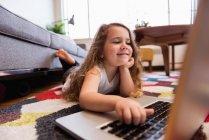 Chica acostada en la alfombra y el uso de ordenador portátil en la sala de estar en casa - foto de stock