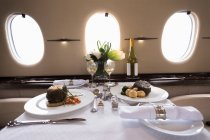 Food and drink served on a table in private jet — Stock Photo