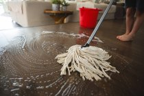 Low section of boy washing the floor with mop at home — Stock Photo