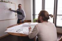 Général mâle discutant graphique sur tableau blanc avec une collègue au bureau — Photo de stock