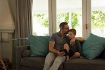 Father and son using digital tablet in living room at home — Stock Photo