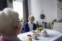 Senior friends interacting witch each other while having breakfast at home — Stock Photo