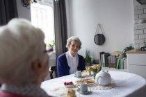 Старший друзів, взаємодіючих відьма один одного в будинку маючи сніданок — стокове фото