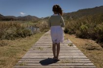 Vista posteriore della ragazza in piedi sul molo su una spiaggia — Foto stock