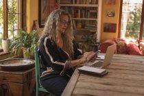 Mujer madura sentada en la silla y usando su teléfono inteligente en casa - foto de stock