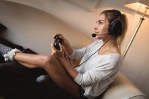 Woman playing video game with headset in living room at home — Stock Photo