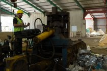 Worker in reflective jacket operating a machine in the scrapyard — Stock Photo