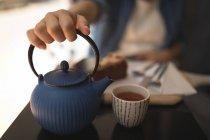 Закри вагітні жінки, що тримає чайник в кафе — стокове фото