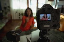 Close-up of camera recording female video blogger in living room at home — Stock Photo