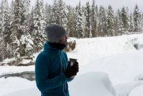 Man having coffee on a snowy landscape during winter — Stock Photo