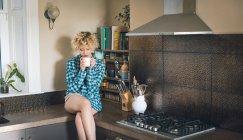Молодая женщина, имеющая в кухне на дому — стоковое фото