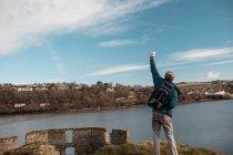Vista posterior de hombre excursionista de pie con la mano levantada en campo - foto de stock