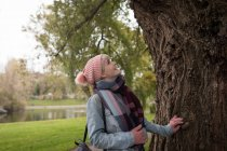 Smiling woman in winter clothing looking at tree in park — Stock Photo